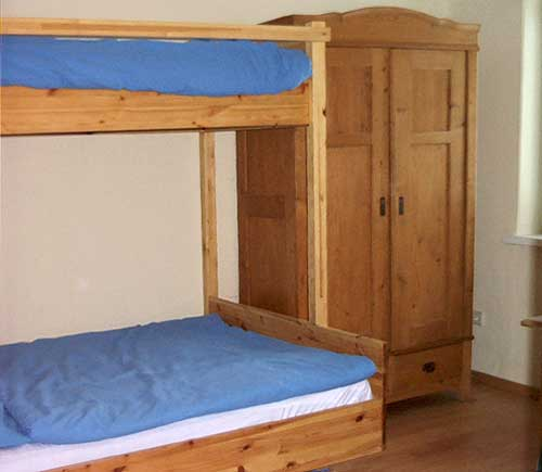 Im Kinderzimmer ist Platz für drei Kids: zwei größere Kleine schlafen im Stockbett, für ein ganz Kleines gibt's ein Gitterbett.